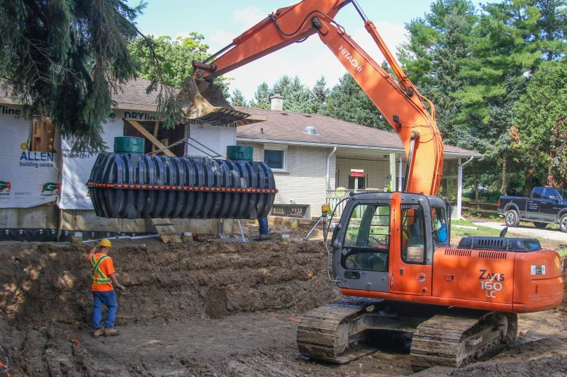 Adam Knoop of Denby Environmental Services operates a Hitachi EX160 excavator while a team member helps guide a new Infiltrator Water Technologies tank into place on a job site. (Photo by Bruce Bell)