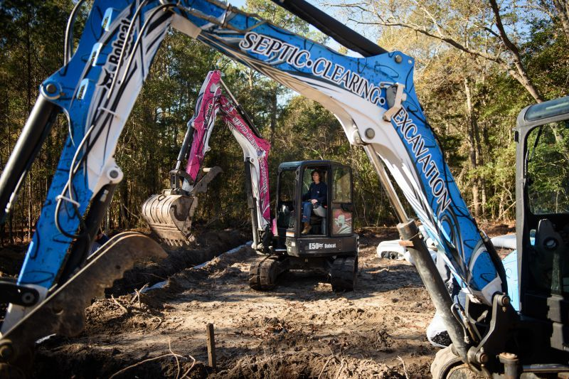Courtney Stephenson, owner of Atlantic On Site Services, works on digging a trench in her pink Bobcat E50 compact excavator as they work on putting in a septic tank system on a job site, next to her second E50, wrapped in blue. (Photo by Andrew Craft)