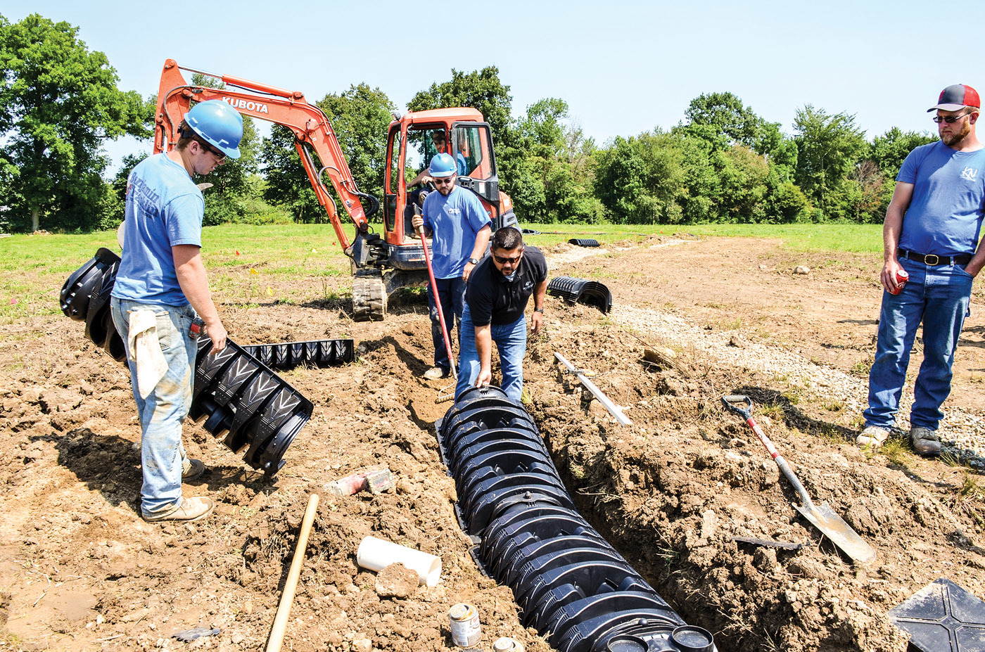 Zak Sherman, of Infiltrator Water Technologies, demonstrates installation of Quick4 low-profile chambers. Also pictured are workers from the DeBord/Benjamin Franklin Plumbing installation team.