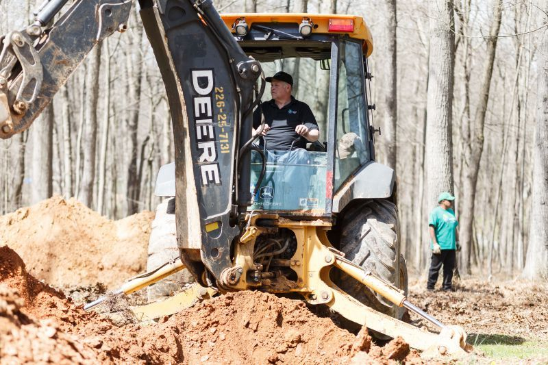 George Schooley, owner of Legacy Septic & Excavation digs a trench with his John Deere 310J backhoe for a deep trench system. (Photo by James Robinson)