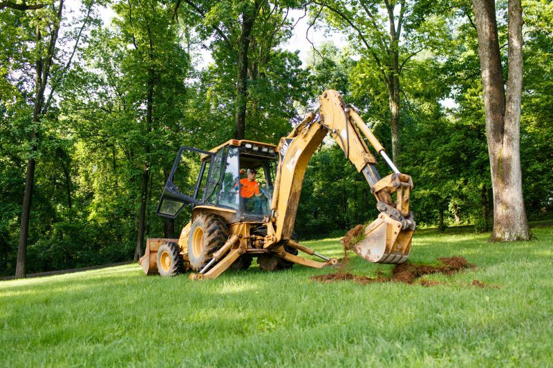 Joe Naggey of McKim Septic digs with a Cat backhoe to find an existing line to tie in a new septic tank. (Photo by James Robinson)