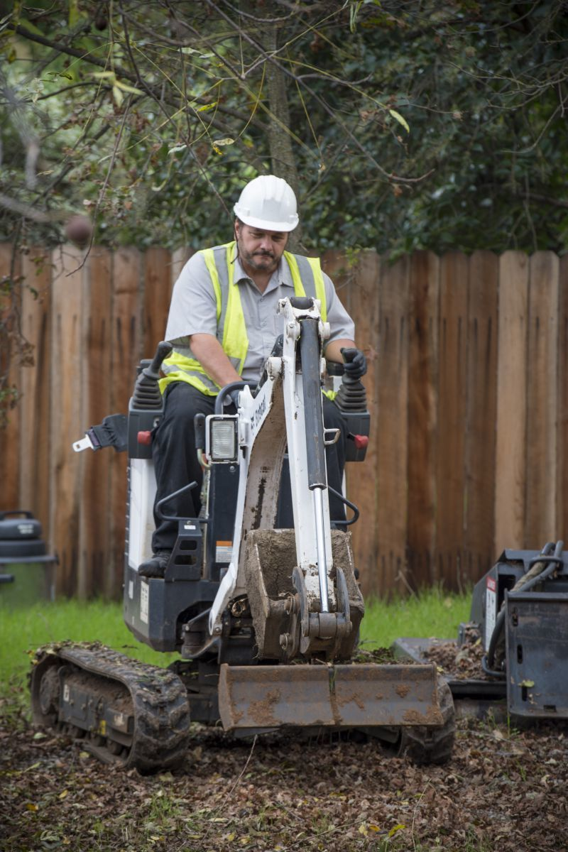 Nick Herrera, owner of NH Construction, loves his compact equipment for getting into tight backyard spaces. Here he works a Bobcat 418 mini-excavator on a residential project. (Photo by Lezlie Sterling)