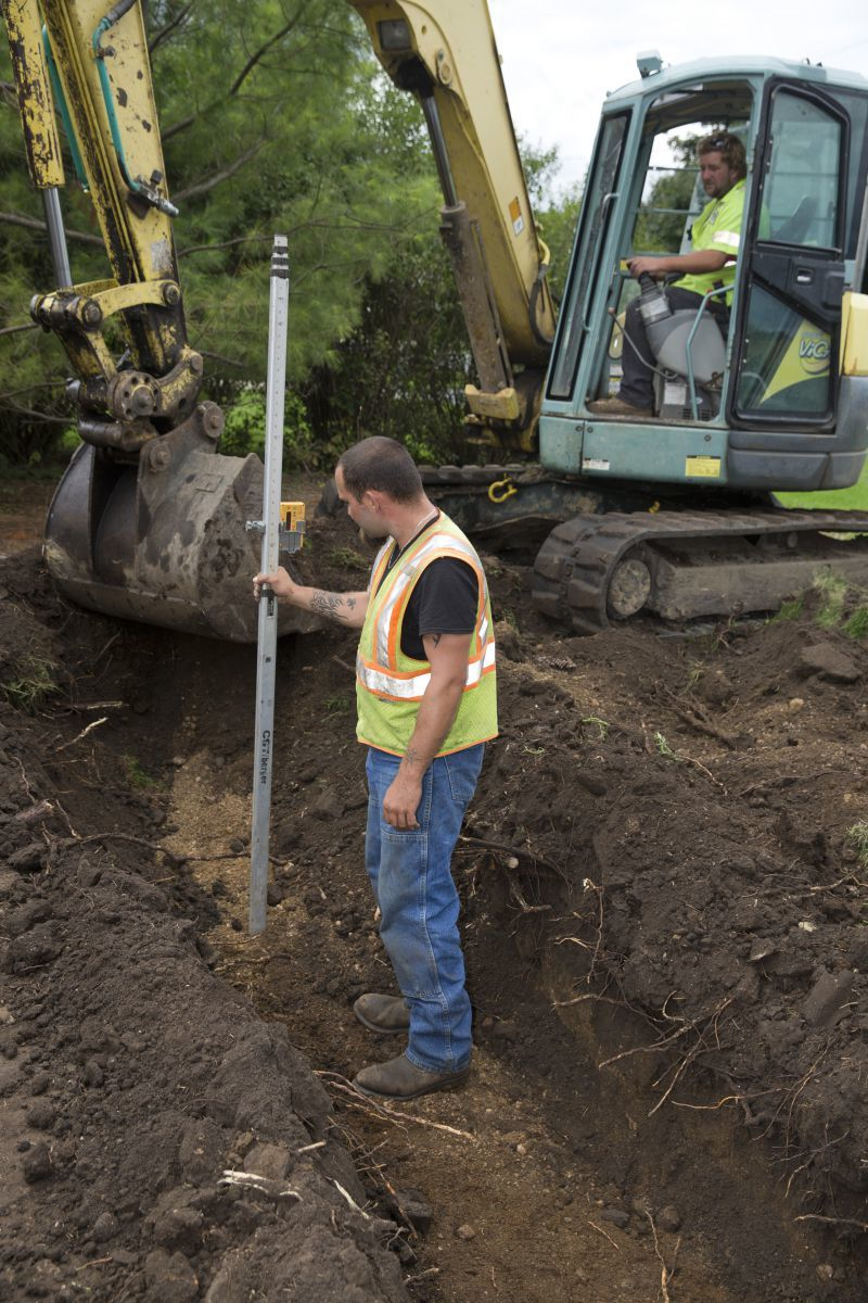 North Iowa Septic Solutions employee Scott Chapin uses a Spectra Precision laser level to measure the depth of a drainfield being dug by Colby Nichols with a Yanmar ViO75 mini-excavator on a septic system installation job. (Photo by Mark Hirsch)