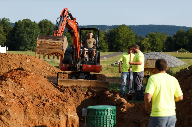 Jerry Stewart, owner of Stewart's Septic Services, digs a trench with a Kubota excavator for a pipe during an installation. (Photo by James Robinson)